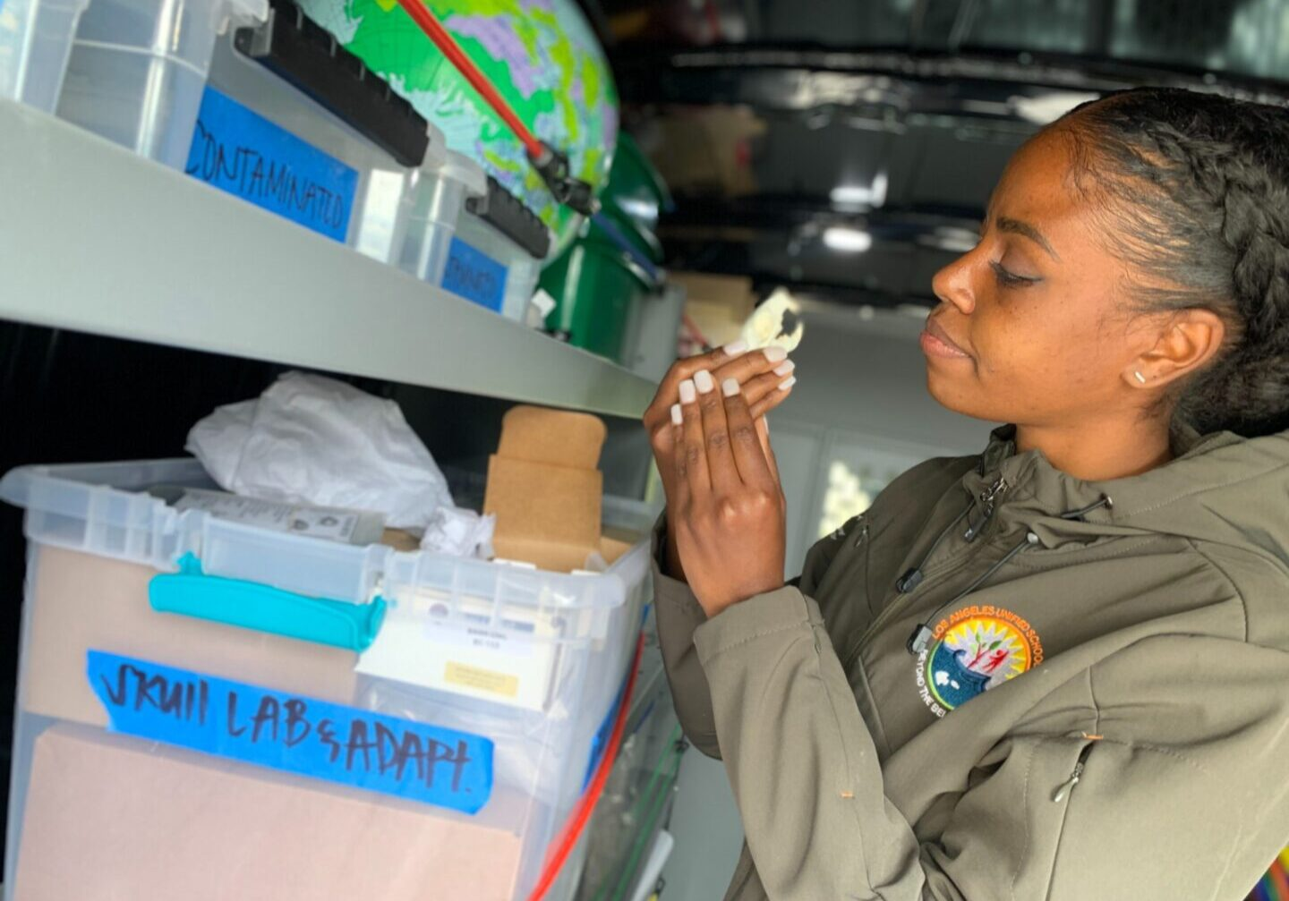 LAUSD outdoor educator Ashley Storey holds a replica skull of a small squirrel. She stands inside the back of the Eco Van, which takes STEM education to children in parks across Los Angeles. (Deepa Fernandes/The California Report)